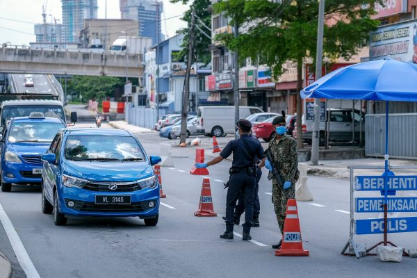 KUALA LUMPUR, MALAYSIA - APRIL 19, 2020 : Malaysia soldier and police inspect road users at a roadblock to enforce the order to stay at home, during the Movement Control Order COVID-19 outbreak.