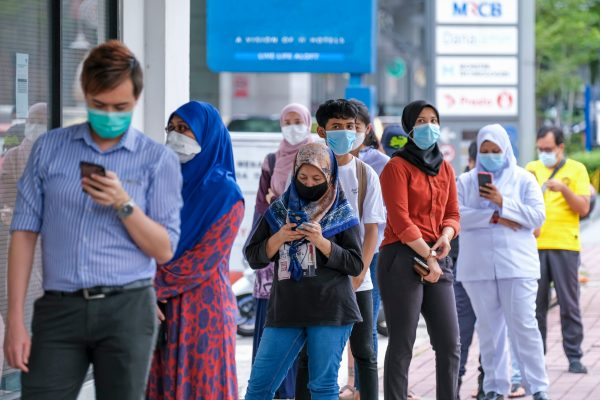 KUALA LUMPUR, MALAYSIA - MAY 04, 2020: People wearing a face mask while lining up with social distancing at the post office. Malaysia Coronavirus disease 2019 (COVID-19) outbreak.